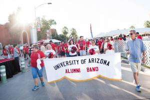 Alumni holding a banner for the Alumni Band Club
